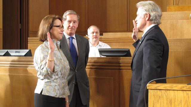 Gov. John Kitzhaber, right, administers the oath of office to Attorney General Ellen Rosenblum as Rosenblum's husband, Richard Meeker, watches at the state Capitol in Salem, Ore., on Friday, Jan. 4, 2013. (AP Photo/Jonathan J. Cooper)