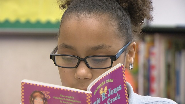 Rosa Parks Elementary student Fortune Gregory reads a Junie B. Jones book in the SuperSensory Literacy Space, May 19, 2015 (KOIN)