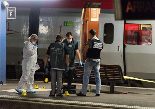 Police officers work on a platform next to a Thalys train at Arras train station, northern France, Friday, Aug. 21, 2015. A gunman opened fire with an automatic weapon on a high-speed train traveling from Amsterdam to Paris Friday, wounding three...