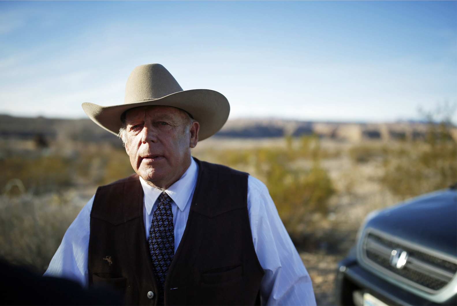 Rancher Cliven Bundy stands along the road near his ranch after speaking with media Wednesday, Jan. 27, 2016, in Bunkerville, Nev. (AP Photo/John Locher)