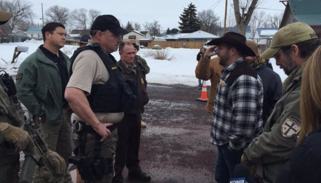 Ammon Bundy (plaid shirt) argues with Harney County deputies and FBI outside their office, Jan. 22, 2016 (KOIN)