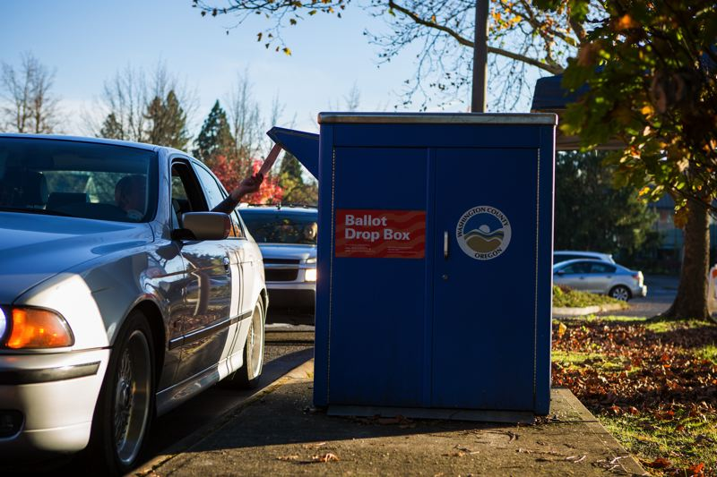 A voter casts his ballot at the drive-up drop box by Tigard City Hall on Nov. 8. (Portland Tribune)_375560