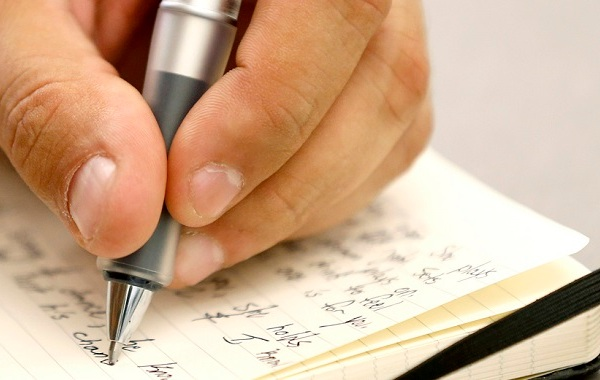 A person writes a note on a piece of paper generic notebook letter pen signature writing_543485