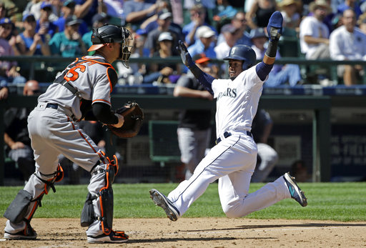 Seattle Mariners' Jean Segura, right, slides safely into home as Baltimore Orioles catcher Caleb Joseph waits for the ball in the fifth inning of a baseball game Wednesday, Aug. 16, 2017, in Seattle. (AP Photo/Elaine Thompson)
