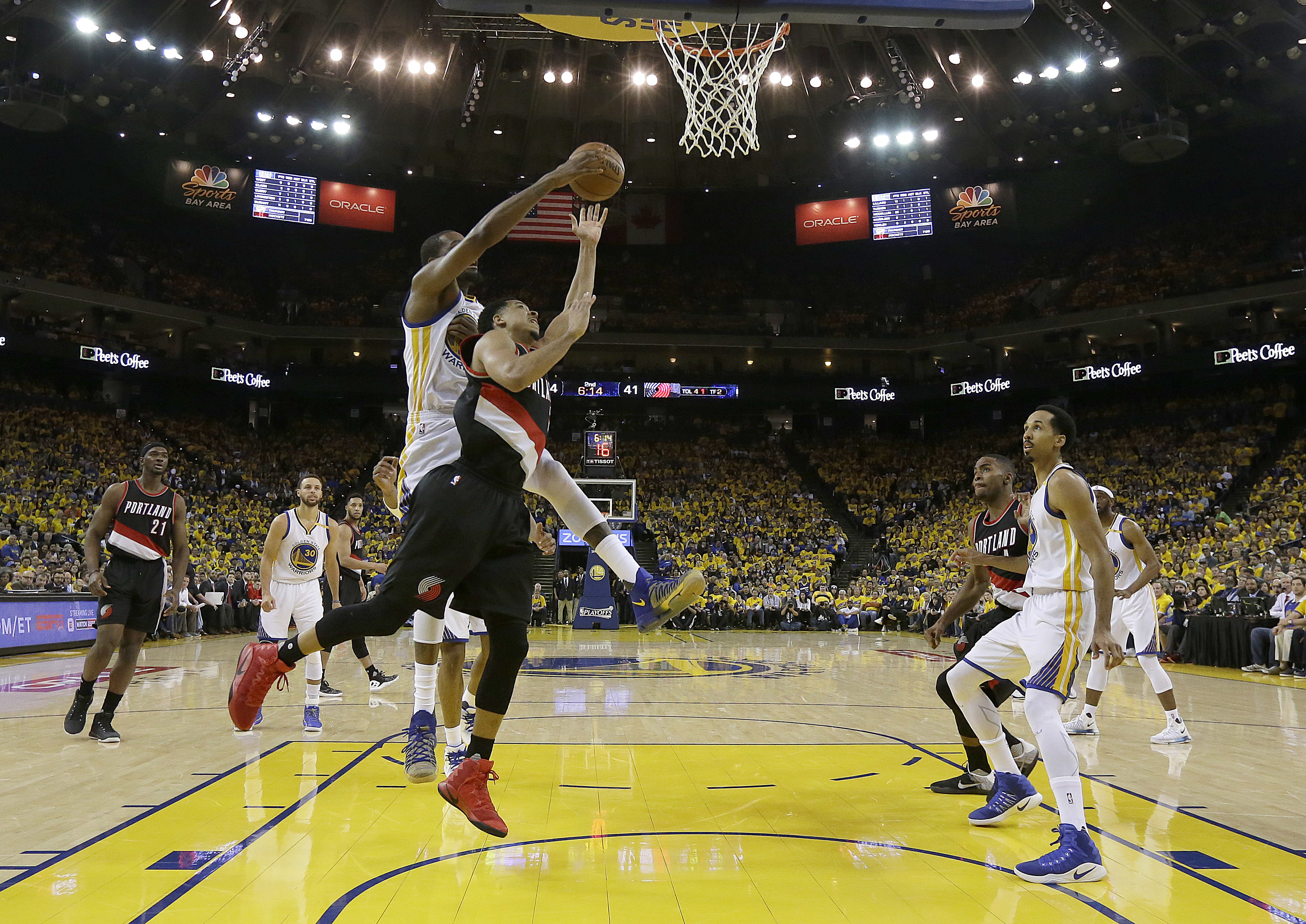 Portland Trail Blazers guard C.J. McCollum, foreground, shoots in front of Golden State Warriors forward Kevin Durant during the first half of Game 1 of a first-round NBA basketball playoff series in Oakland, Calif., Sunday, April 16, 2017. (AP...