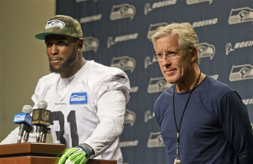 Seattle Seahawks' Kam Chancellor, left, and head coach Pete Carroll talk about Chancellor's return to the team after holding out over a contract dispute, during NFL football news conference at the team's headquarters in Renton, Wash., Wednesday,...