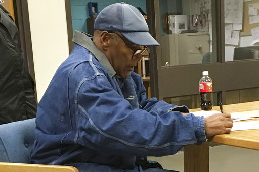Former football legend O.J. Simpson signs documents at the Lovelock Correctional Center, Saturday, Sept. 30, 2017, in Lovelock, Nev. Simpson was released from the Lovelock Correctional Center in northern Nevada early Sunday, Oct. 1, 2017. (Brooke...